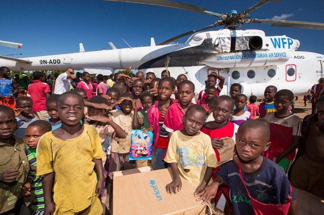 Malawian children crowd around a Russian Mi8 helicopter being used by the United Nations, World Food Program to deliver food aid to areas still cut off by the flooding, around Bangula and Mkhanga.