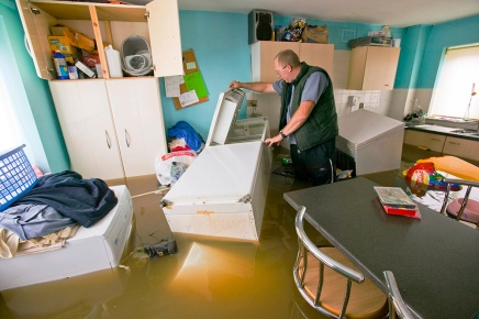 A marooned resident searches for food inside a flooded house in Toll Bar, South Yorkshire,UK. The village was hit by unprecedented floods during June 2007 and cut off for over a week.